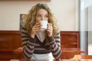 woman holding tea cup sipping coffee and thinking about something-perhaps what she had learned in 2019.