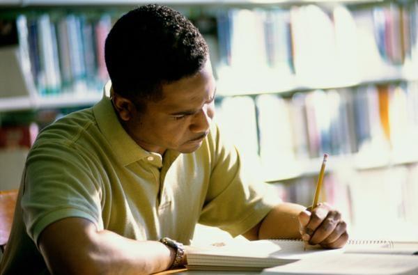 Man sitting at a desk writing his resume.